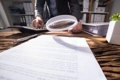 Empresário Looking At Document com lupa imagens de stock