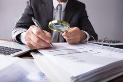 Empresário Looking At Receipts através da lupa fotografia de stock