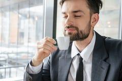 Empresário na ruptura de café no copo de cheiro de assento do restaurante do café delicioso fotos de stock