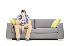 Empresário novo preocupado que senta-se em um sofá Fotos de Stock Royalty Free