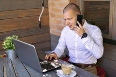 Empresário novo que senta-se no café com o portátil, falando por p foto de stock royalty free
