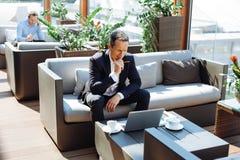Empresário profissional esperto que pensa sobre seu projeto imagem de stock