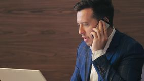Empresário que chama pelo smartphone ao usar o caderno para trabalhar no escritório filme