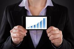 Empresário que mostra o gráfico no telefone celular imagem de stock