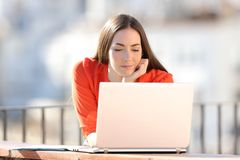 Empresário que olha o índice em linha do portátil em um balcão fotos de stock royalty free