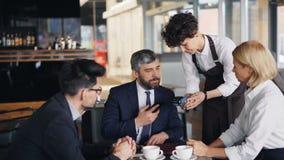 Empresário que paga pelo almoço de negócio usando o smartphone e falando aos colegas de trabalho video estoque