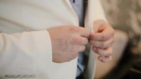 Empresário que prepara-se para um trabalho, pondo seu terno formal A ideia do close-up das mãos masculinas abotoa um revestimento vídeos de arquivo