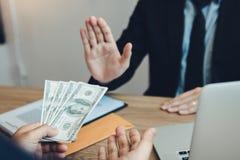 Empresário que recusa o dinheiro dado subôrno pelo sócio com anti conceito da corrupção da corrupção fotografia de stock royalty free