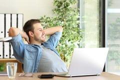 Empresário que relaxa e que pensa no escritório imagem de stock