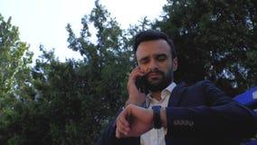 Empresário que usa um telefone celular num parque num banco. homem falando em um celular. homem barbudo falando em um smartphone. filme