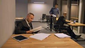 Empresário seguro do chefe com os colegas que trabalham com documentos no escritório da noite video estoque