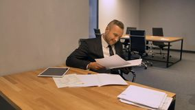 Empresário seguro do chefe que trabalha com documentos no escritório da noite interno filme