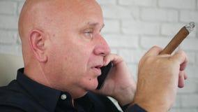 Empresário Smoke um charuto e uma conversa Flavored ao telefone celular video estoque