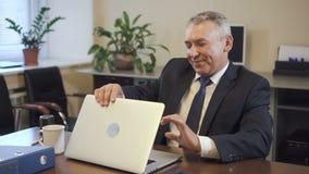 Empresário superior no terno que trabalha no laptop no escritório filme