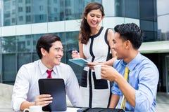 Empresários asiáticos que trabalham fora com café Fotos de Stock