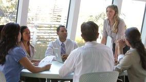 Empresários assentados em torno da tabela que tem a reunião video estoque