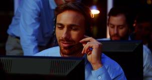 Empresários com auriculares usando o computador no escritório filme