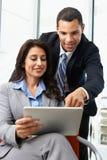 Empresários com a tabuleta de Digitas durante a reunião informal imagem de stock royalty free