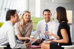 Empresários com a tabuleta de Digitas que tem a reunião no escritório foto de stock