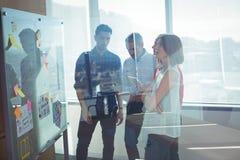 Empresários de negócio que estão pelo whiteboard visto através do vidro imagens de stock