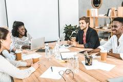 empresários de sorriso multiculturais que discutem a estratégia empresarial durante o seminário foto de stock royalty free