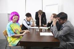 Empresários multi-étnicos cansados com o colega na peruca cor-de-rosa na reunião foto de stock