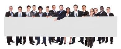 Empresários multi-étnicos que guardam o quadro de avisos vazio Imagem de Stock Royalty Free
