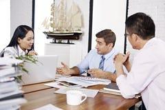 Empresários multinacionais que discutem o desempenho de vendas dentro fora Imagens de Stock Royalty Free