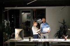 Empresários no escritório na noite que trabalha tarde fotos de stock royalty free
