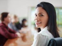 Empresários no quarto de reunião e no sorriso da mulher Imagens de Stock
