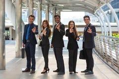 Empresários novos energéticos, três homens de negócios e dois Busine Imagens de Stock