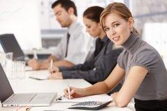 Empresários novos que sentam-se na tabela de reunião fotos de stock