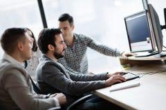 Empresários novos que trabalham no computador no escritório imagem de stock