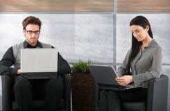 Empresários novos que usam o portátil Fotografia de Stock Royalty Free