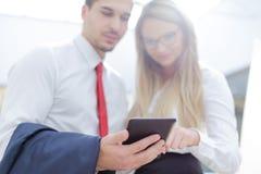 Empresários novos que usam a tabuleta no centro de negócios imagens de stock royalty free