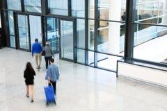 Empresários que apressam-se através do corredor, borrão de movimento Fotos de Stock Royalty Free