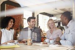 Empresários que encontram-se na cafetaria disparada através da janela fotografia de stock