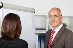 Empresários que estão pelo flipchart Fotografia de Stock Royalty Free