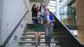 Empresários que interagem um com o otro ao andar em escadas vídeos de arquivo
