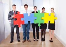 Empresários que montam o enigma de serra de vaivém Imagens de Stock Royalty Free