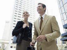 Empresários que olham afastado contra o prédio de escritórios Fotografia de Stock