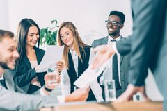 empresários que olham documentos quando sócios multirraciais que têm a conversação imagens de stock