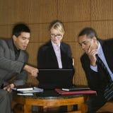 Empresários que olham o portátil Imagens de Stock Royalty Free