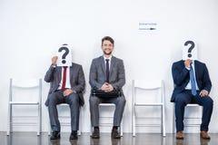 Empresários que sentam-se na fila e na entrevista de espera, guardando pontos de interrogação no escritório foto de stock