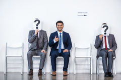 Empresários que sentam-se na fila e na entrevista de espera, guardando pontos de interrogação no escritório imagens de stock