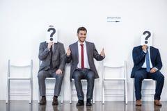 Empresários que sentam-se na fila e na entrevista de espera, guardando pontos de interrogação no escritório imagens de stock royalty free
