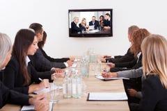 Empresários que sentam-se na tabela de conferência Foto de Stock Royalty Free