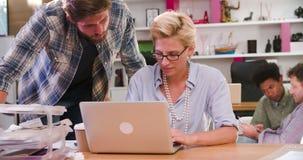 Empresários que trabalham no portátil no escritório ocupado video estoque