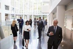 Empresários que usam a tecnologia na área ocupada da entrada do escritório fotos de stock royalty free
