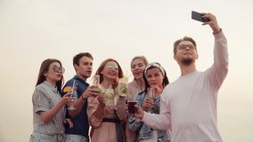 Empresa amigável e alegre, vidros do tinido com os cocktail bonitos no smartphone da câmera Ver?o urbano vídeos de arquivo
